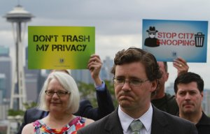 Attorney Ethan Blevins, in foreground, leads a news conference, Thurs., July 16, 2015, in Seattle, on filing a privacy lawsuit against the city of Seattle, arguing that the city is violating people's privacy rights by having garbage collectors look through people's waste to see if they are throwing away food scraps or other items that should be going in the yard waste bin.